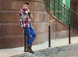 Young tattooed man posing on blurred building background