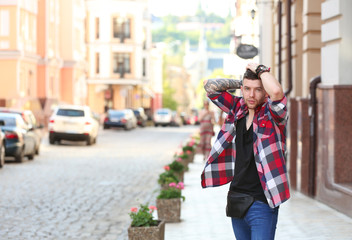 Young tattooed man posing on blurred city street background