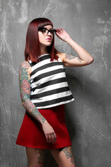 Beautiful girl with tattoo on color background