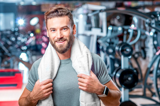 Lifestyle portrait of handsome muscular man standing with towel after the training in the sport gym