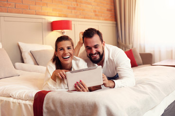 Happy couple resting in hotel room