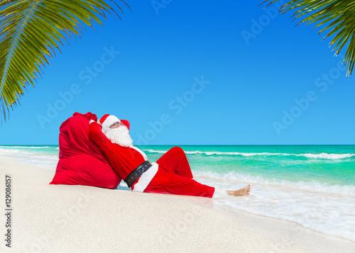 Santa Claus Sunbathing On Christmas Gifts Sack At Ocean Palm Beach