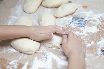 child prepares the dough of flour for pasta pastry bread
