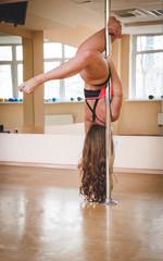 Pole dancer, girl posing near pylon