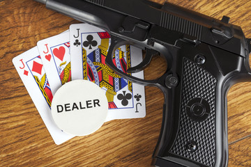 Illegal gambling concept with handgun and poker hand and dealer chip