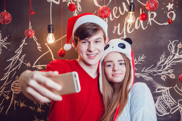 Happy couple in funny hats standing hugging and make selfie on a dark background with Christmas pattern. New year.