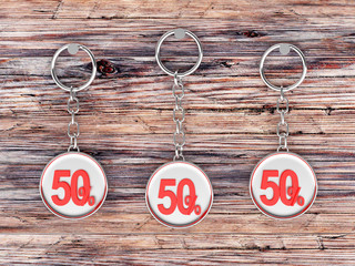 Set of three silver keychains with red 50 percentage discount on wooden background. 3D illustration
