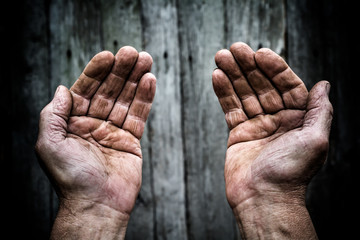 A man holds his hands in front of him. Hands on top.