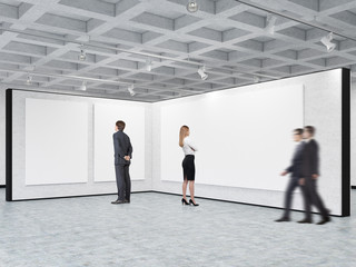 Man and woman are looking at blank posters in a gallery