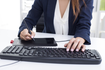 Woman with tanned fingers is working with her pen tablet and a k