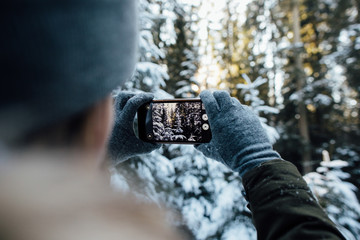 Girl takes a picture of snow-covered trees in the winter forest.