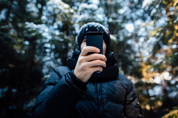Man  takes a picture on mobile phone in the snow-covered pine forest on a cold winter day.