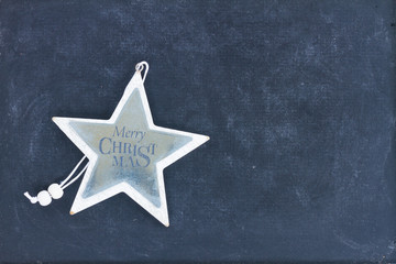 Merry Christmas star on black wooden background with copy space
