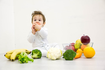 baby surrounded with fruits and vegetables, healthy child nutrition
