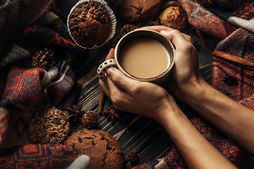 stylish rustic winter picture with hands holding warm coffee coo