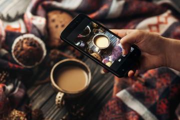 hand holding phone taking photo of stylish winter flat lay coffe