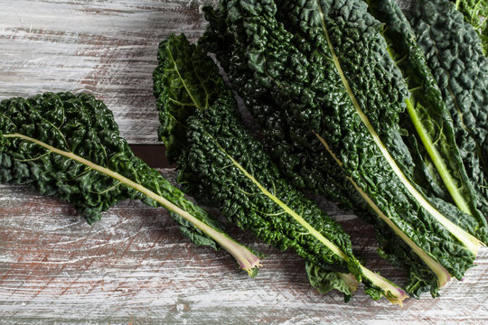 Above shot of organic lacinato kale on brown wood table above shot