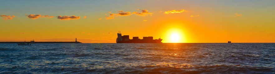 Panoramic view of cargo ship in sunset sea