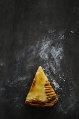 Piece of pear frangipane tart. Dark background, copy space