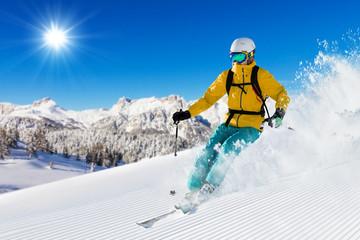 Skier on piste running downhill