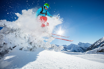 Fototapete - Freeride skier jumping from rock