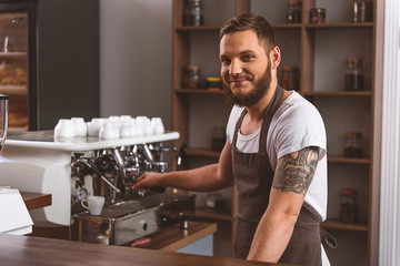 man in apron smiling in cafe