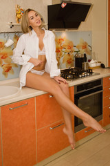 Sexy woman sitting on kitchen table