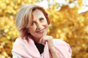 Closeup portrait of gorgeous middle aged woman in autumn park