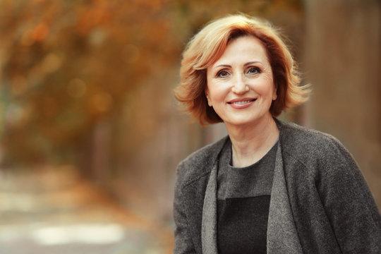 Portrait of gorgeous middle aged woman in autumn park