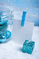 Glass jar with christmas decorations, gift and paper for text