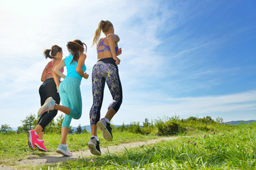 Three Female Joggers running together outdoors