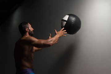 Muscular Man Exercise With Medicine Ball