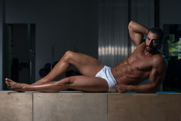 Man In Underwear Resting On Box After Exercise