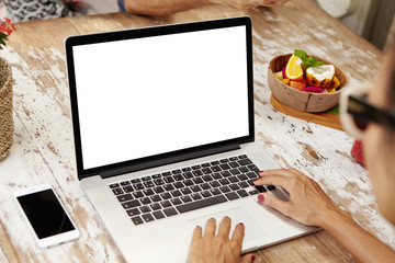 People, leisure and technology. Female using wi-fi on laptop computer, browsing internet, shopping online, sitting at wooden table at cafe. Stylish female chatting with friends via social networks