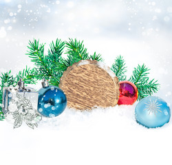 Christmas background. Round wooden board, branches of green fir and christmas decorations on snow