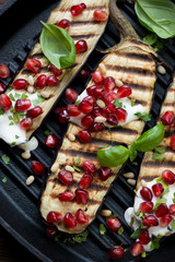 Grilled aubergine with pomegranate, sour cream, nuts and basil