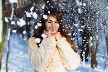 Portrait of young girl in snow forest outside. Winter concept.