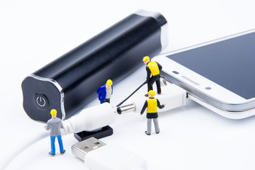 Miniature tiny toys team of engineers are doing connected cable