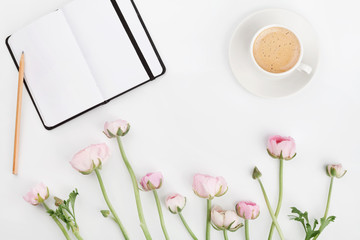 Beautiful spring Ranunculus flowers, empty notebook and cup of coffee on white desk from above. Greeting card. Breakfast. Pastel color. Clean space for text. Flat lay style.
