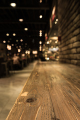 Empty wood table top of bar with blur of cafe restaurant in dark