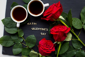 """The inscription """"Happy Valentine"""" on a black background with red roses and coffee"""