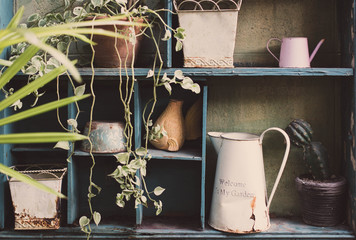 Garden tools and flowerpots on wood shelf background with vintage feel