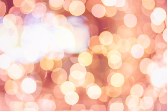 Bokeh background. Blurred light in warm tone background. Store shop mall Christmas and  New Year  concept. with soft focus dream city blurry rich pink, orange and golden bubble light wallpaper