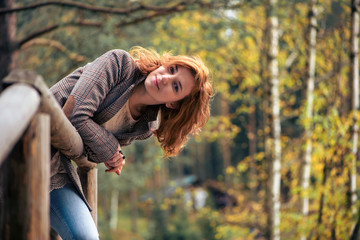 Red-haired girl in a tweed jacket standing on a wooden bridge, o