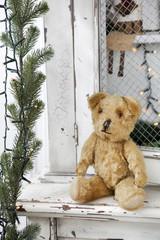 Vintage teddy-bear sitting on the wardrobe