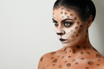 portrait of a girl on a white background. isolated. face art. body art. hairstyle. black hair. wild cat. facial profile
