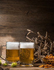 Mugs beer, hops, pretzels, spikelets on empty wooden background