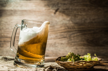 Beer spills from tankard on empty wooden background