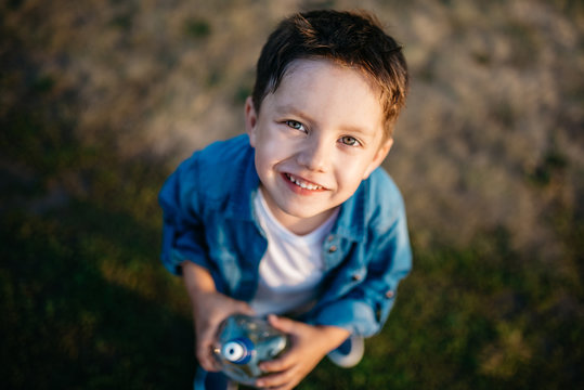 Portrait of a beautiful little boy 3-4 years old, holding a plastic bottle of water. View from above. Outdoors, summertime. Green and withered grass on a blurred background