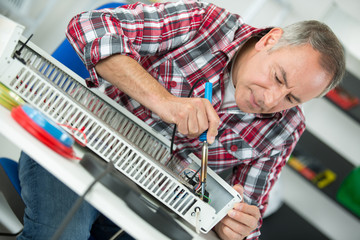 middle-age man plumber fixing radiator